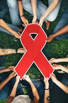 Group of people holding a red colored ribbon