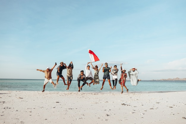 Group of people jumping together on the beach for celebrating indonesia independence day