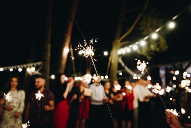 Group of people lighting bengal lights together. togetherness.