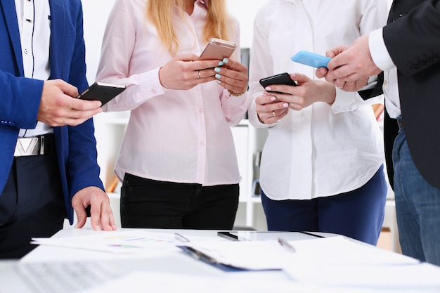 Group of people look at phones in arms at office closeup.