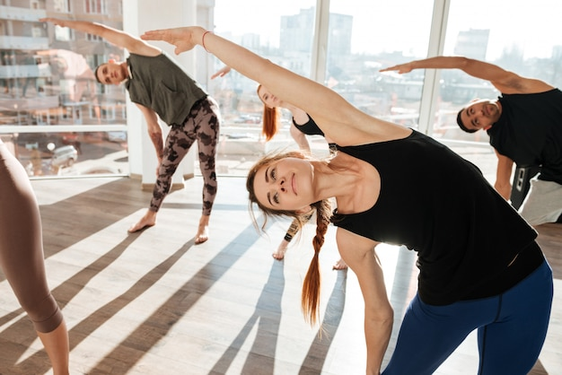 Group of people making exercises in yoga class