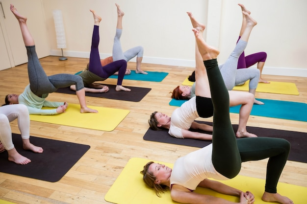Group of people performing chakrasana on exercise mat