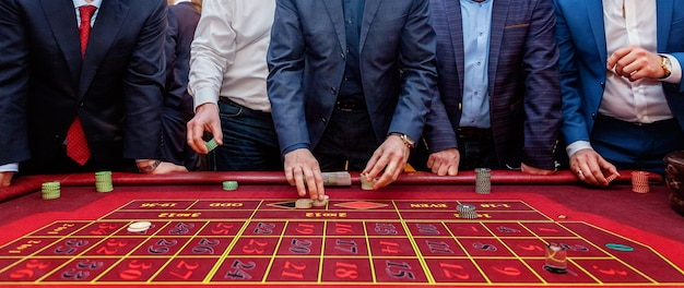 Group of people playing poker at roulette table with tape measure