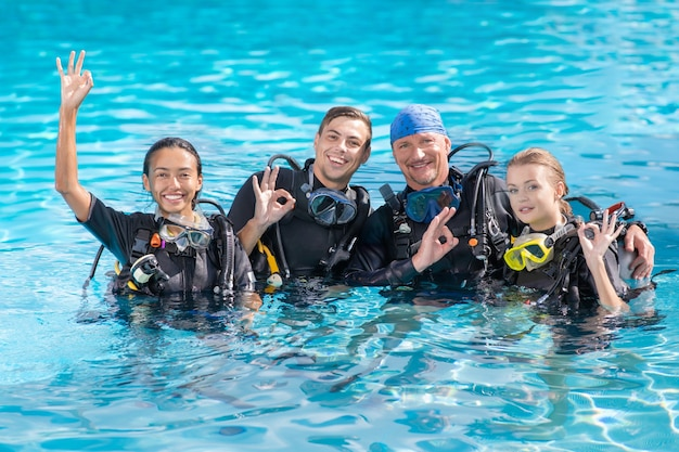A group of people practice scuba diving in the pool