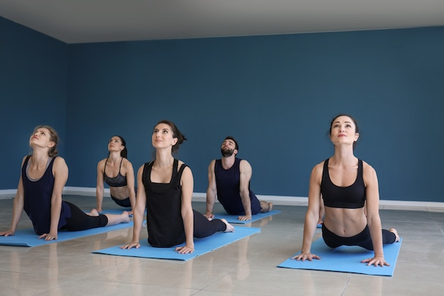 Group of people practicing yoga in gym