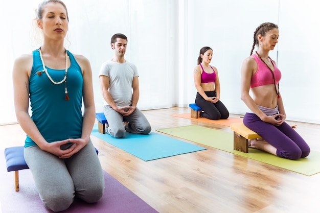 Group of people practicing yoga at home. vajrasana pose.