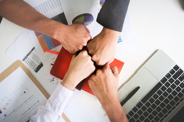 Group of people putting their hands working together on wooden