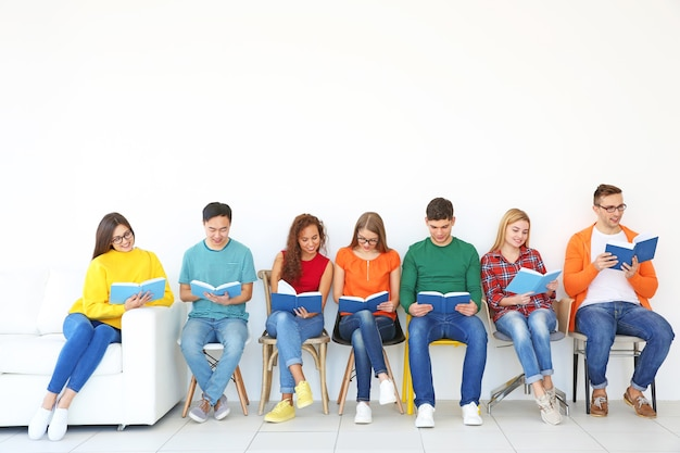 Group of people reading books while sitting near light wall