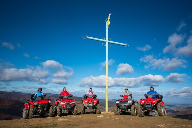 Group of people on red quad bikes near cross with a symbol of ukraine on top of the mountain