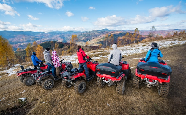 Group of people on red quad bikes