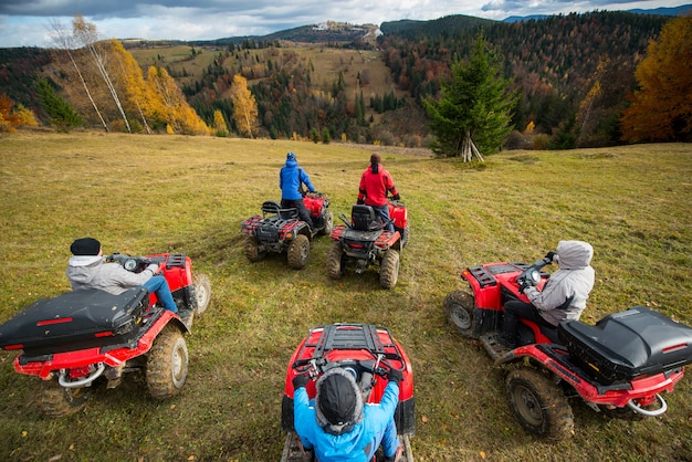 Group of people riding a quad bikes on hill