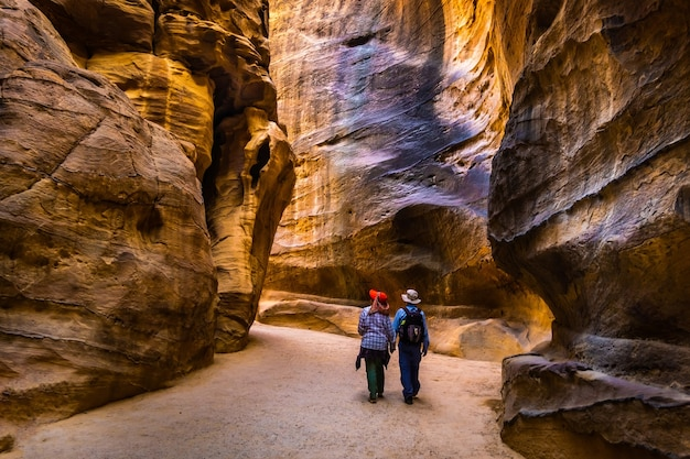 Group of people between sandstone rocks at narrow path in petra jordan