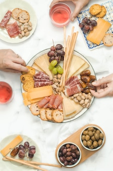 Group of people sharing a cheeseboard and sausages in a celebration brunch. food concept