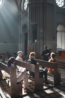 Group of people sitting on the bench and listening to speech of priest during mass