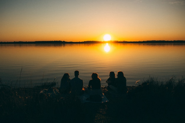 Group of people sitting by the sea enjoying the beautiful view of the sunset