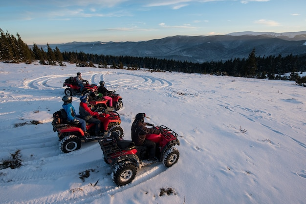 Group of people sitting on off-road four-wheelers atv bikes