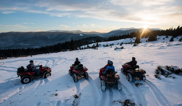 Group of people sitting on off-road quad bikes, enjoying beautiful sunset in the the mountains in winter