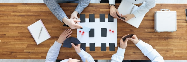 Group of people sitting at table and playing board games top view rest and leisure concept