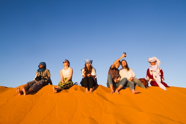 Group of people sitting on top of dune