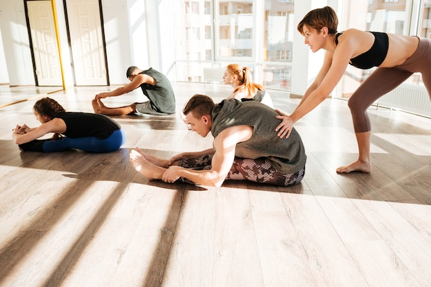 Group of people stretching and practicing yoga with trainer