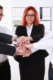 Group of people in suits crossed hands pile