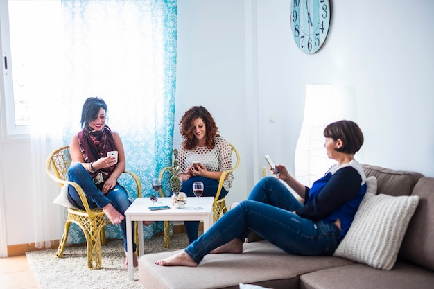 Group of people three caucasian beautifl female friends stay at home using cellular smartphone together. everyone do his own activity work or leisure no interacting with friends
