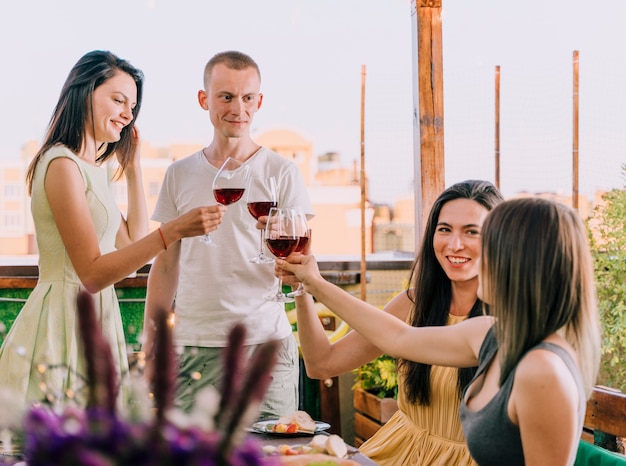 Group of people toasting at rooftop party