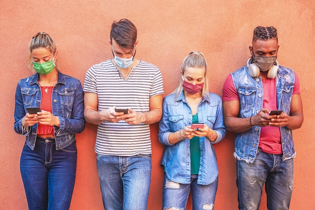 Group of people using their smartphones in covid 19 times protected with face mask - friends checking online news while standing by the wall and holding cellphones