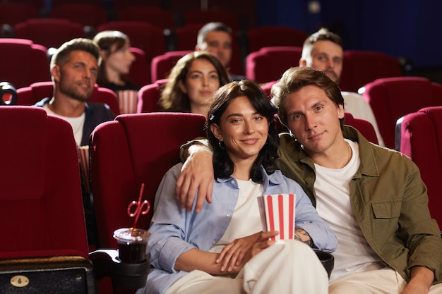 Group of people watching movie in cinema, focus on smiling young couple embracing and looking at camera while sitting on red velvet chairs in front row, copy space