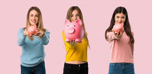 Group of people with colorful clothes holding a piggybank on colorful background
