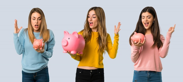 Group of people with colorful clothes surprised while holding a piggybank on colorful background