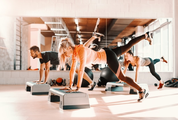 Group of people with healthy habits doing exercises for legs on steppers. gym interior. in background mirror with their reflection.