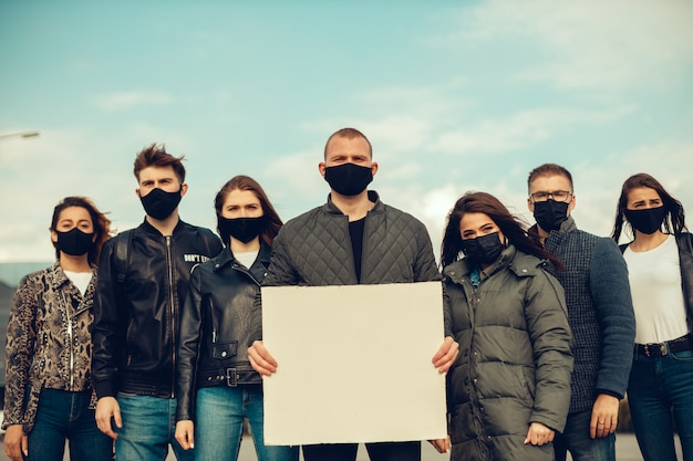 A group of people with mask and posters to protest the protest of the population against coronavirus and against the introduction of quarantine