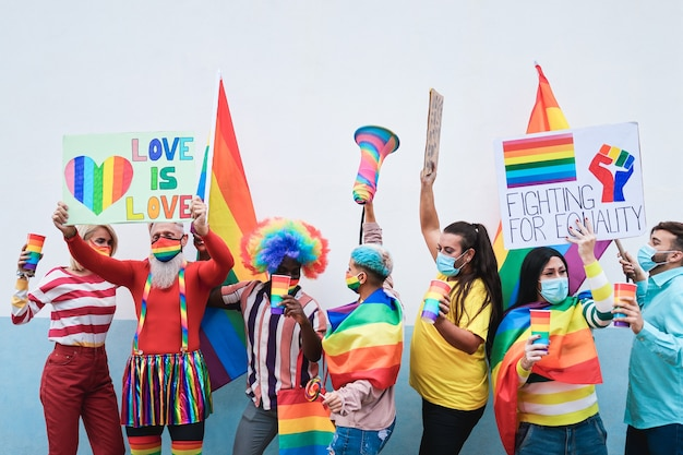 Group of people with rainbow flags and banners dancing at gay pride event