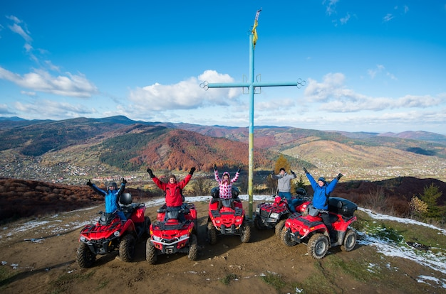 Group of people with raised hands up on red quad bikes near cross with a symbol of ukraine on top of the mountain