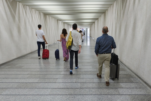 Group of people with suitcases on wheels go through the underpass rear view