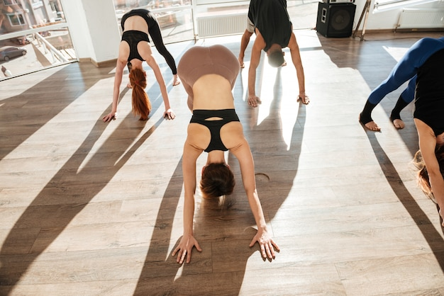 Group of people working out and practicing yoga in studio