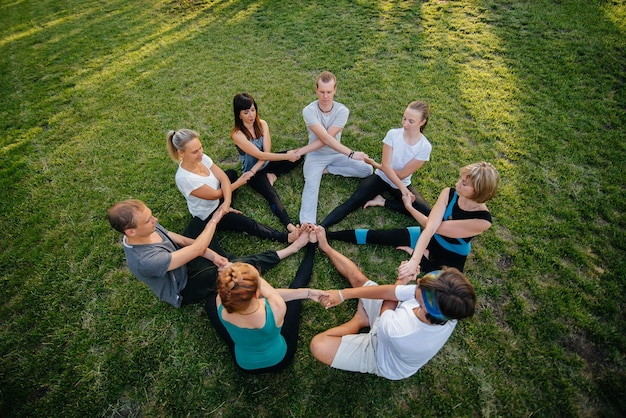 A group of people do yoga in a circle in the open air during sunset
