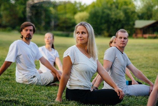 A group of people do yoga in the park at sunset.