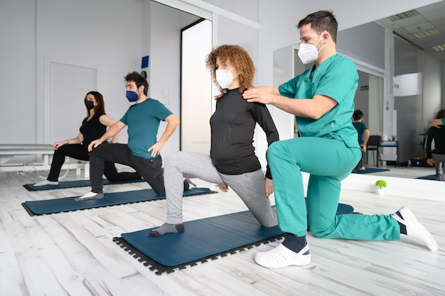 Group of persons on yoga mats assisted by physiotherapist at the rehabilitation clinic.