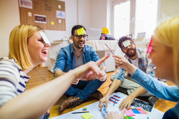 Группа коллег, сидящих в кругу и играющих в игры и весело проводящих время.