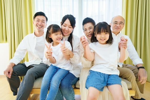 部屋にいる3世代家族の集合写真