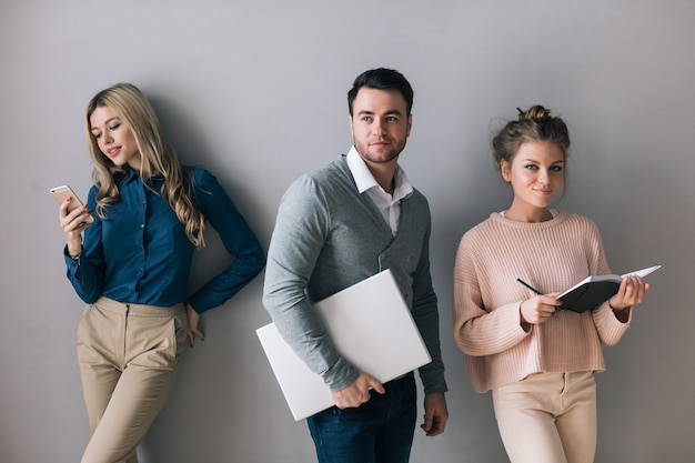 회색 벽에 서있는 회색 남자와 두 예쁜 여자의 단체 사진