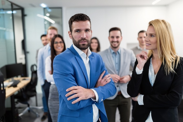 オフィスでポーズをとって成功したビジネスチームの集合写真