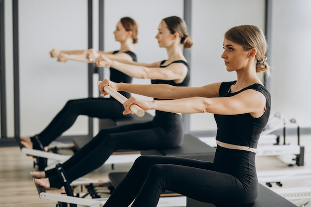 Group of pilates instructors exercising on reformers