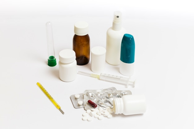 Group of pills, medicine cans, spray, syrups and syringes on a white background