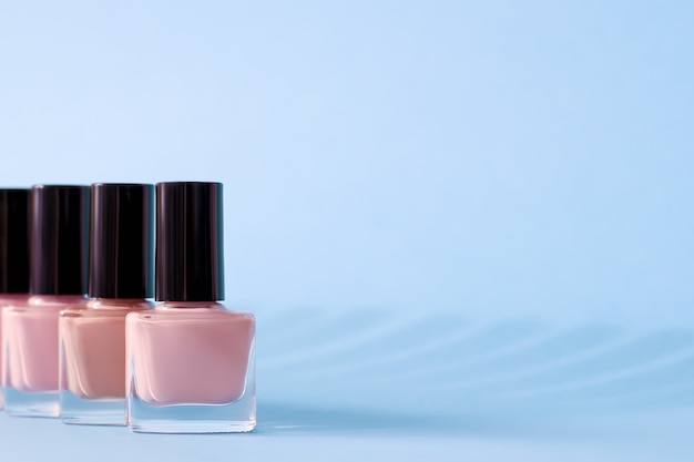 Group of pink nail polishes on blue surface.