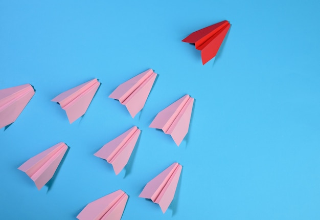 Group of pink paper planes follow the first red against a blue background. the concept of uniting a team to achieve goals, a strong leader, a highly effective group, top view