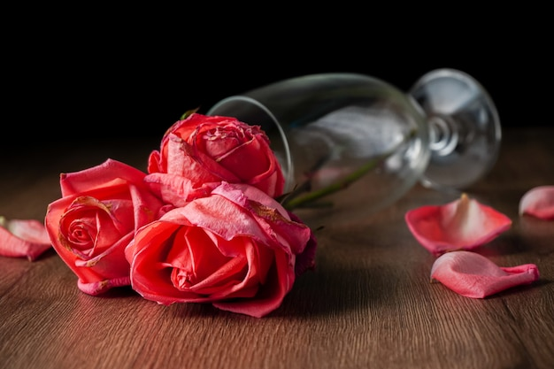 A group of pink roses put in champagne glass that falling on dark color wooden table