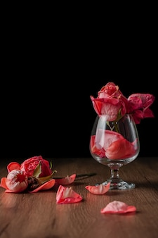 A group of pink roses put in wine glass that falling on dark color wooden table